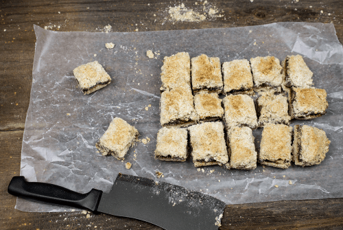 batch of date squares cut and assembled on wax paper