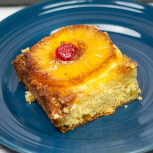 piece of pineapple upside down cake on blue plate with slice of pineapple and maraschino cherry on top