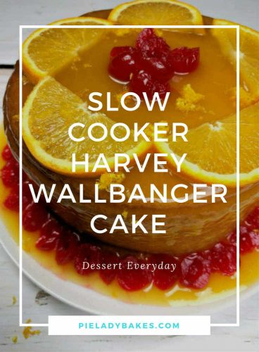A Harvey Wallbanger Cake with orange slices, maraschino cherries on a white plate, with text Slow Cooker Harvey Wallbanger Cake in white lettering with white frame for pinterest and logo pieladybakes.com in blue letters on the bottom of the image.