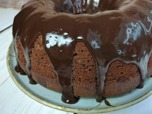 side view of chocolate buttermilk bundt cake with chocolate frosting dripping on the sides