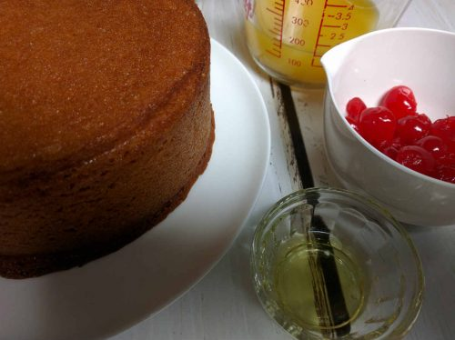 freshly baked cake on a white plate with ingredients for orange glaze, orange juice, cherries and galliano