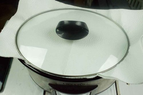 Slow cooker with clear glass lid and black handle on top of paper towels while cake bakes in slow cooker