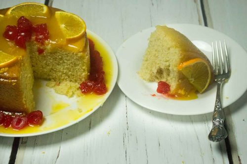 slice of harvey wallbanger cake on a white plate with silver fork to the side, and the remaining cake to the left showing the slice removed