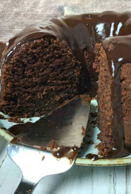 chocolate bundt cake with slice removed shows cake server