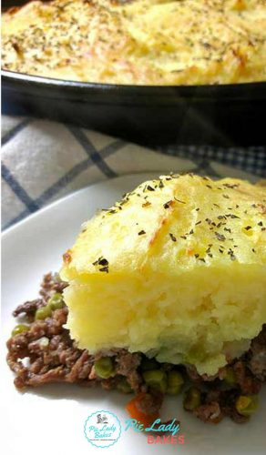 slice of Shepherd's Pie on white plate with cast iron skillet and remainder of shepherd's pie in the background