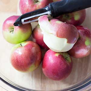 10 Mcintosh apples in a glass bowl with apple peeler