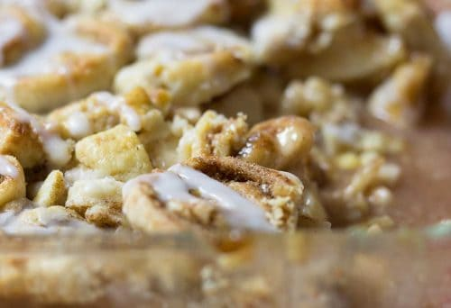 closeup image of apple crisp topped with cinnamon pie crust and powdered sugar glaze