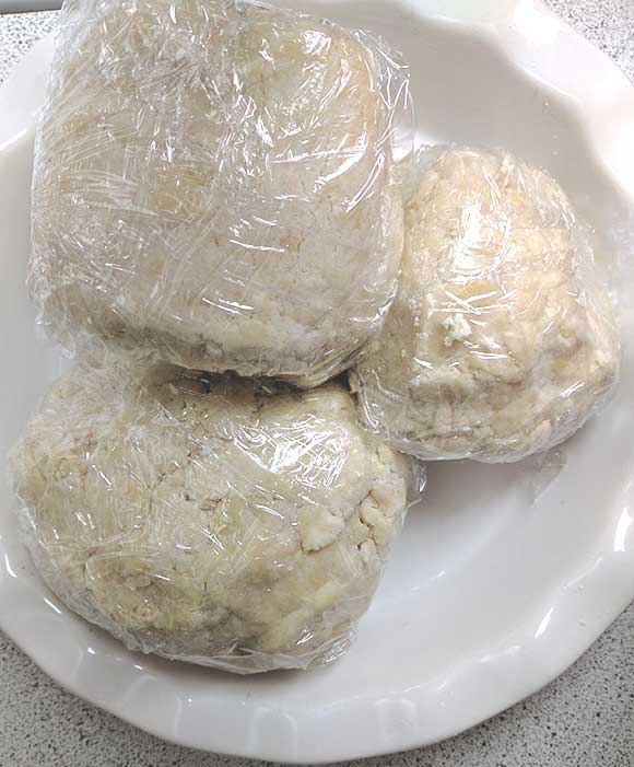 pastry dough shaped into balls, wrapped in plastic and ready to chill, perfect flaky pie crust