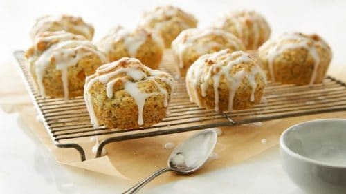 lemon yoghurt poppy seed muffins on a wire baking rack and a spoon in the foreground