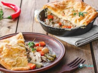 recipe image of puff pastry topped Chicken Pot Pie on a brown plate with brown fork, shows cast iron skillet in background with serving removed, and red chili pepper to the left