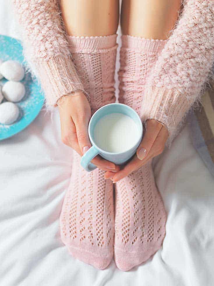 woman in pink socks with pink sweater, holding blue mug of milk, with blue dish and cookies to the side