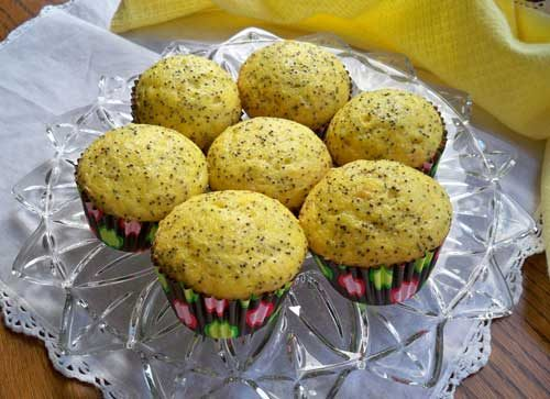 7 lemon poppy seed muffins with multi coloured paper muffin cups on a glass plate
