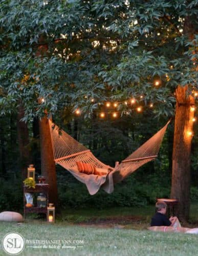 canvas hammock with orange pillow between two posts with tree branches overhead filled with fairy lights