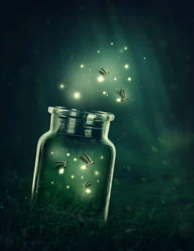 mason jar full of fireflies on a green misty background