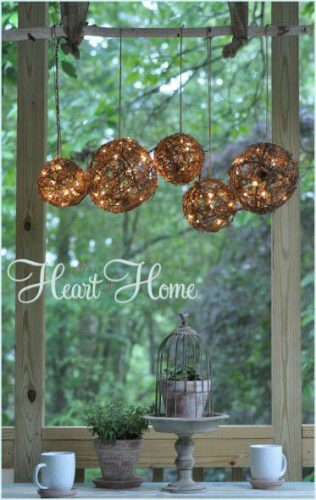 glittering globes hanging outdoors with text hear home in white lettering