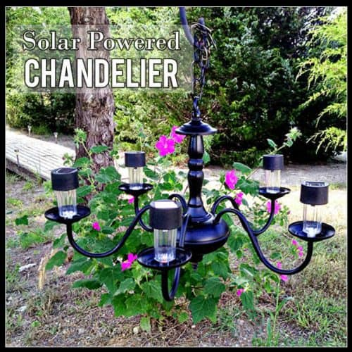 black iron chandelier with pink flours and trees in background and solar lights