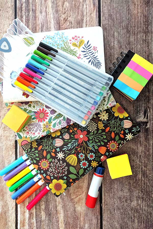 coloured journals, pens, markers, stickers, glue stick all bullet journal supplies