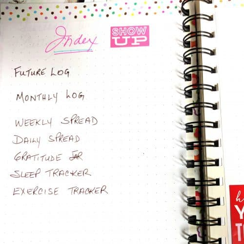 Index in pink lettering, shows list of bullet journal items handwritten with pink sticker