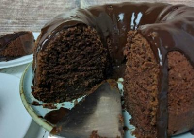 chocolate cake with servings removed shows moist chocolate cake inside and lots of chocolate glaze over the cake part of the cake server is showing on a blue plate