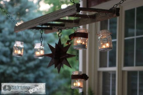 a ladder chandelier and tin star shows clear glass jars hanging from ladder and lights in inside next to a building