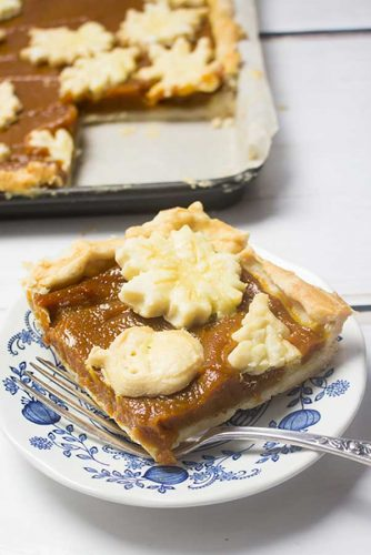 square piece of pumpkin pie with blue floral dessert plate and fork with slab pie showing pieces removed in the background