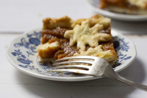 square piece of pumpkin pie shows oak leaf made of pastry, on blue delft china plate with silver fork