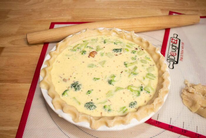 broccoli quiche ready to go into the oven with rolling pin on a dough ez rolling mat