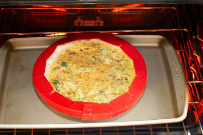 broccoli quiche with piecrust shield on a tray in the oven