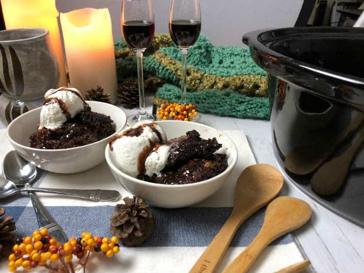 two dishes of smores crockpot chocolate lava cake, two glasses of kahlua, candles and table decorations