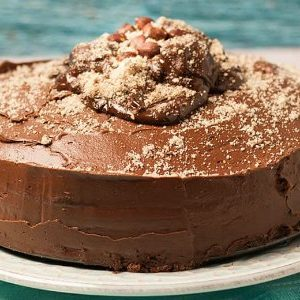 side view of chocolate fudge cake with chocolate buttercream icing and chocolate caramels and almonds on top