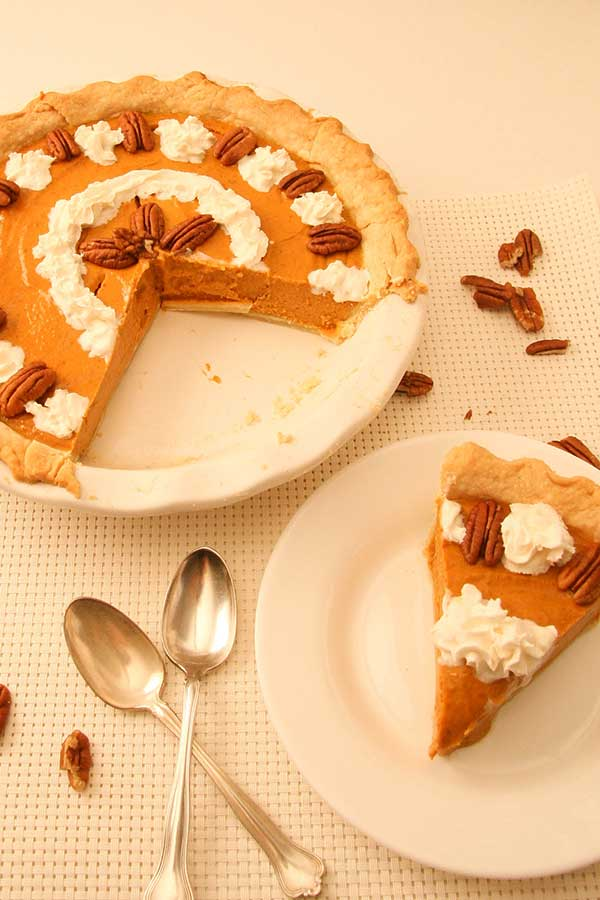 slice of gluten free pumpkin pie on white plate beside whole pumpkin pie and two spoons