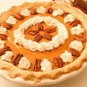 whole gluten free pumpkin pie garnished with pecans and whipped cream