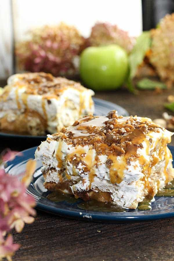 two slices of apple pie cheesecake lasagna with caramel sauce