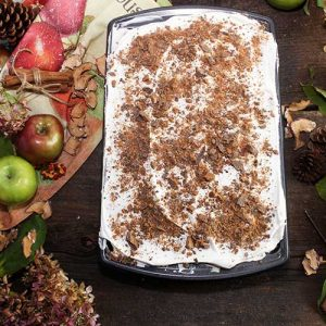apple pie cheesecake lasagna in baking pan with apples and decorations in the background