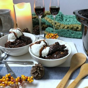 smores crockpot lava cake in two white bowls, with table decorations, candles and two wine glasses with kahlua