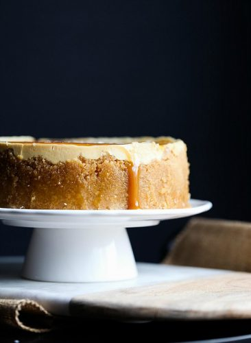 side view of salted caramel cheesecake on a white pedestal cake plate with a dark background