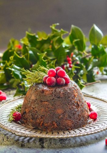 christmas pudding on a white plate with holly in the background and red berries on top of pudding