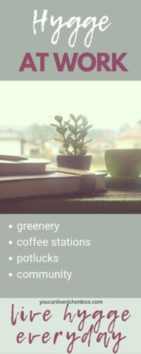 picture of desk, books, green plant and coffee in front of office window