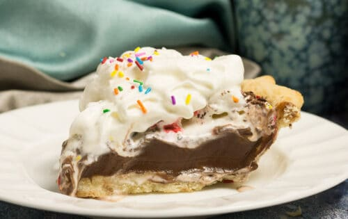 slice of chocolate pudding pie on a white china plate topped with whipping cream and multi coloured sprinkles. shows two blue coffee mugs and blue napkins in background