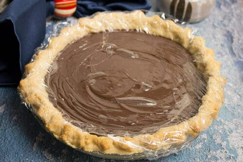 overhead image of chocolate cream pie with plastic film on top of the pie filling