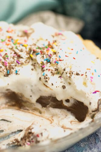 partly eaten chocolate pie with lots of whipped cream shows coloured sprinkles and whipped cream dripping down onto the pie plate