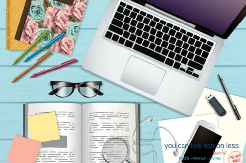 flatlay of desk items laptop glasses book pens journal phone and paper on a blue wooden table top
