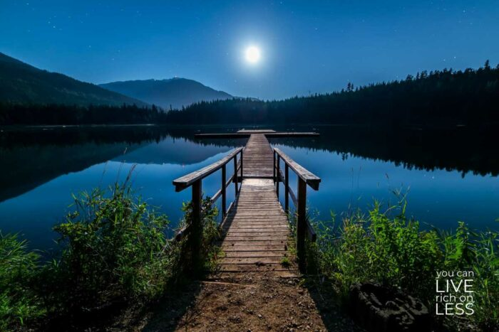 long dock over a lake with mountains in the background and a full moon in the sky