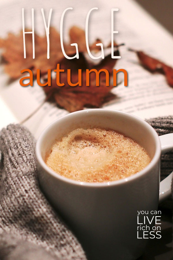 mug of coffee held with arms covered by long sleeved sweater that is gray, book and autumn leaves in the background