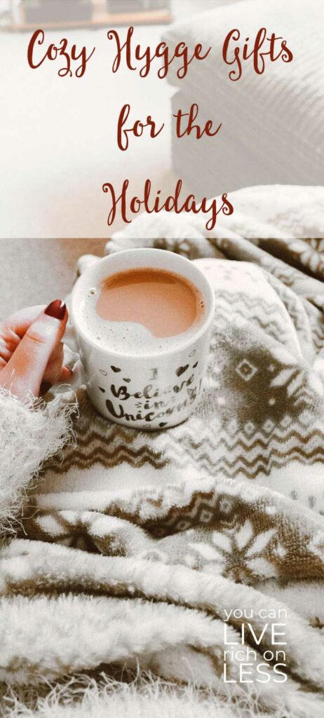 closeup view of woman holding a coffee cup, wrapped in cozy blankets with the text cozy hygge gifts for the holidays in script font on top