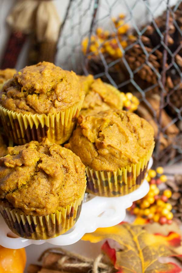 pumpkin muffins on a white dish with fall decorations in the background