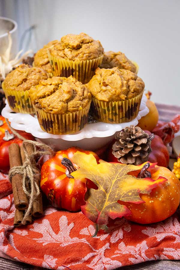 pumpkin muffins on a white dish with an orange napkin and fall decorations around it