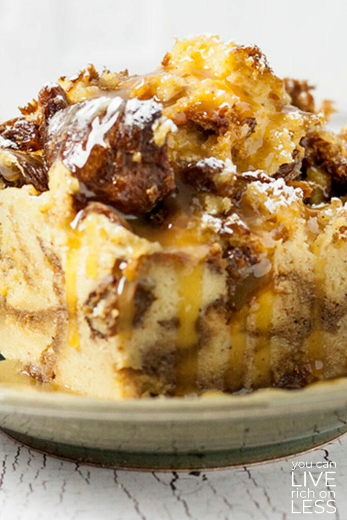 close up of bread pudding with caramel sauce on a light brown dish white weathered wood table top