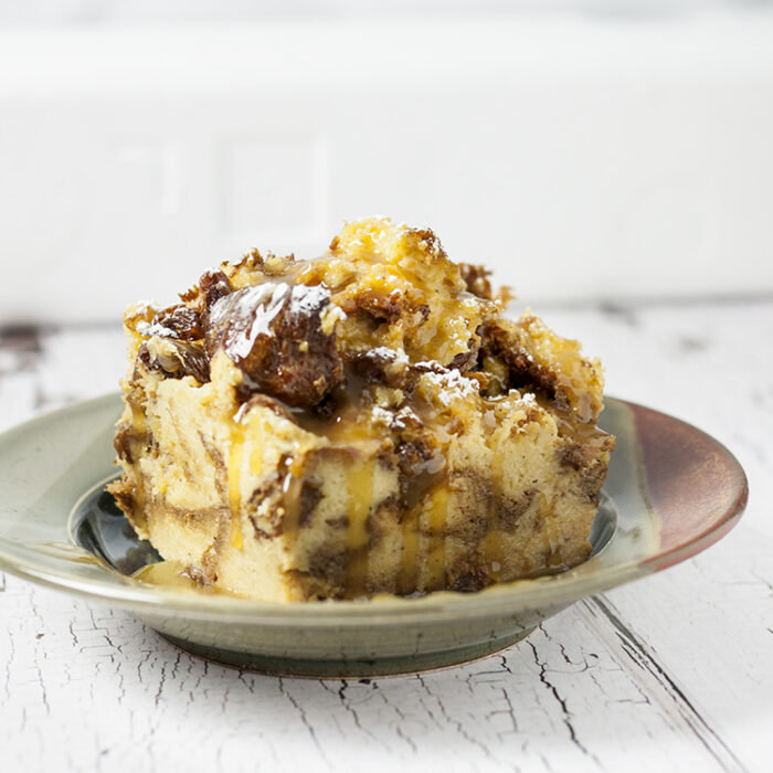 large serving of panettone bread pudding in a two toned pottery dish white background and table top