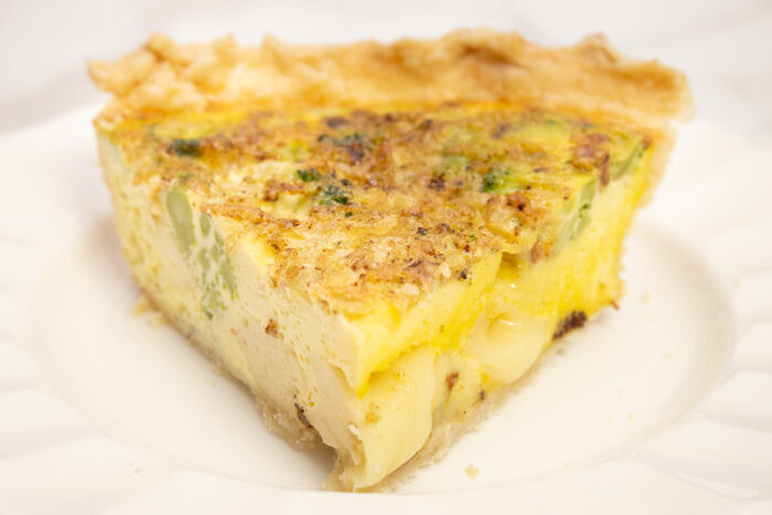 broccoli quiche slice on a white plate